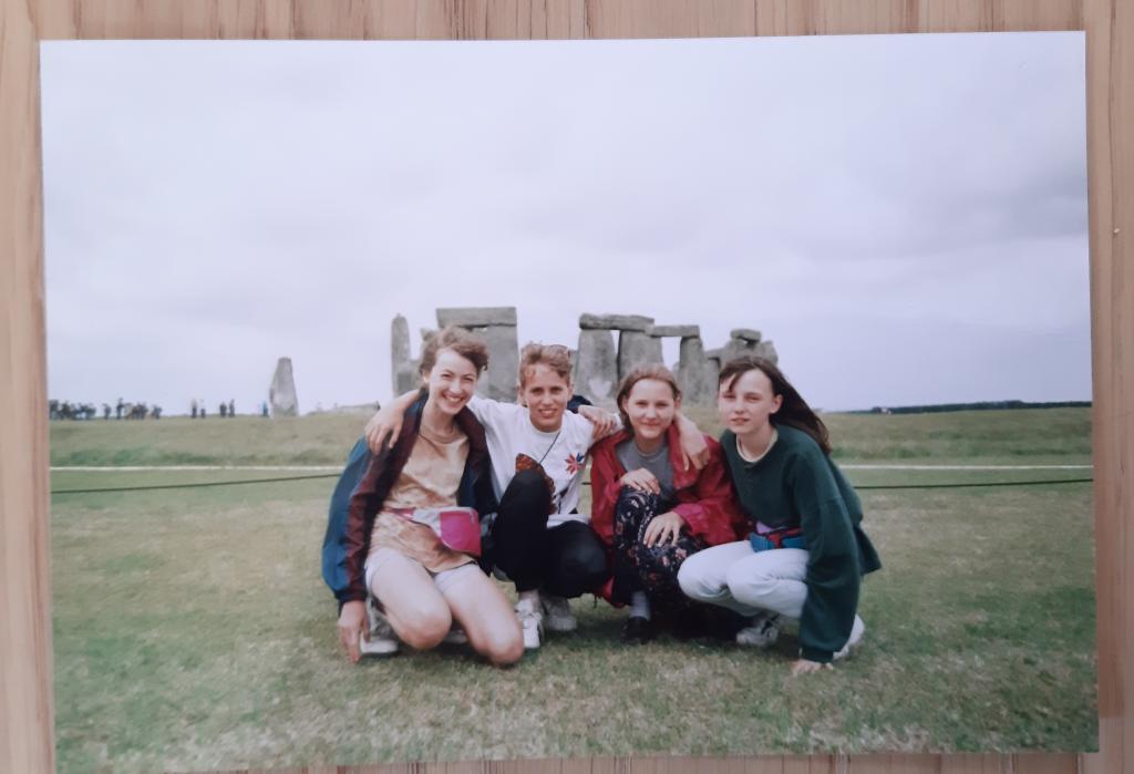 Fotka čtyř kamarádek držících se za ramena před Stonehenge.